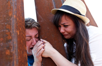 A reunion between mother and daughter from opposite sides of a massive steel fence at the United States-Mexico border. Originally printed in the New York Times.